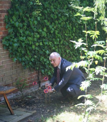 Headmaster planting a poppy in memory of Frank Helps - former CRGS student who was killed in action at this time 100 years ago